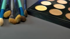 A makeup palette with some brushes lying beside it,the shot is moving from right Stock Footage
