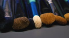 Footage of several brushes lying on a table, the shot is moving from the left Stock Footage