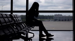 Stressed girl in airport nervously tapping foot and talk on phone, silhouette Stock Footage