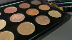 Footage of a make up palette and some brushes lying beside it,the shot is moving Stock Footage