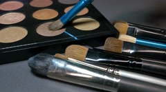 A moving shot from left to right along a make up palette, a person takes a brush Stock Footage