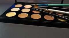 A make up palette lying on a table with some brushes lying on it Stock Footage