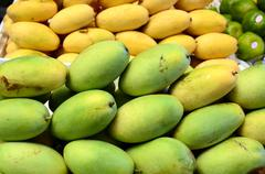 Fresh green unripe mango fruit symmetrically stacked Stock Photos