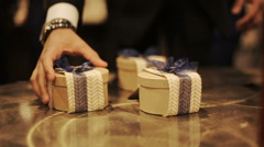 Little present boxes decorated with blue ribbons stand on the wooden table Stock Footage