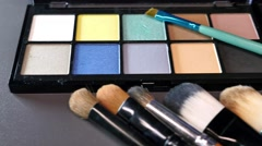 A moving shot showing a professional make-up palette with some brushes in front Stock Footage