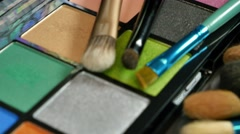 A moving shot showing a make up palette and some brushes lying next and on it Stock Footage