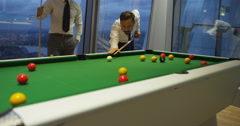 4k, Business people playing billiards after work in the evening. Slow motion. Arkistovideo