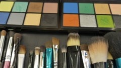 Footage of a colorful make-up palette and a lot of brushes lying on the table Stock Footage