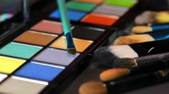Footage of a make up palette lying on a table with some brushes lying beside Stock Footage