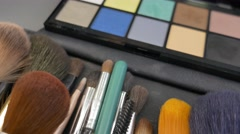 Close up and a moving shot of a make up palette and some brushes lying beside Stock Footage