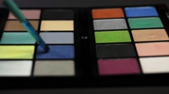 Two make up palettes standing next to each other, a make up artist uses a color Stock Footage