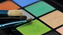 Three brushes lying on a make-up palette. the shot is going out of focus Stock Footage