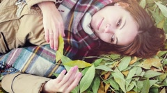 Top view of autumn romantic woman lying over leaves and smiling in slowmotion Stock Footage
