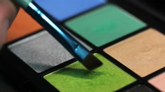 Extreme close up shot of a make up palette and a make up artist using its green Stock Footage