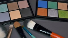 Two makeup palettes standing next to each other, some brushes in front of them Stock Footage