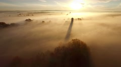 Foggy,breathtaking sunrise landscape with long shadow of silo Stock Footage