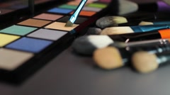 A make up palette with some brushes beside it and a makeup artist using a color Stock Footage