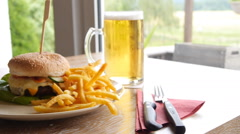 Lunch with burger, frites and beer, slider and slow motion Stock Footage