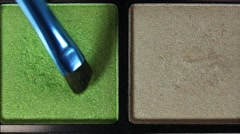 Close up shot of a green color from a make up palette and a person applies it Stock Footage