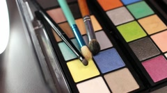 Footage of a professional make up palette with three brushes lying on it Stock Footage