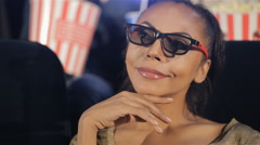 Woman in 3D glasses holds her hand near her chin at the movie theater Stock Footage