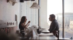 Having rest in cafe. Young man and woman have a meal, talk, laugh. Nice view on Stock Footage