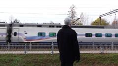Man watch high speed train rush at railroad, back half length portrait Stock Footage