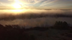 Sunrise over surreal landscape with fog over river shore Stock Footage
