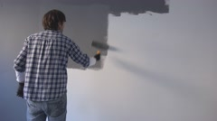 Male painter and interior decorator painting wall with gray color Stock Footage