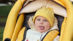 Baby sitting in the baby carriage showing tongue Stock Footage