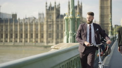 4K Portrait smiling London businessman with bicycle outdoors in the city Stock Footage