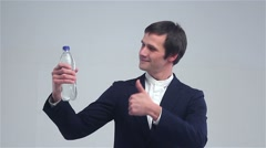Young man showing a bottle of water and shows great Stock Footage