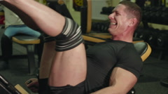 Athlete doing exercise at the leg muscles at the gym with his coach Stock Footage