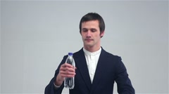 Young man opens a bottle and drink water Stock Footage