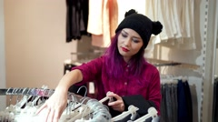 Asian woman choosing clothes on rack in a showroom Stock Footage