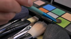 A make-up palette and some brushes in front of it, a person uses a color Stock Footage
