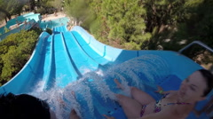 Young boy with woman drive off the water slides, slow motion  Stock Footage