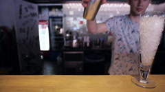 Bartender is pouring a cocktail from shaker in wineglass with ice at bar counter Stock Footage
