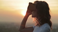 Woman uses a virtual reality glasses at sunset Stock Footage