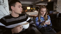 Young couple in cafe. Male drinking coffe while female using smartphone Stock Footage