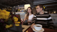 Happy couple of frends sitting in cafe using laptop and laughing Stock Footage