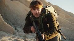 Armed Terrorist Walking in Desert Environment.  Stock Footage