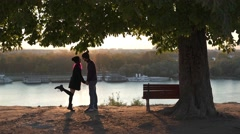 Couple kissing at sunset uner a tree Stock Footage