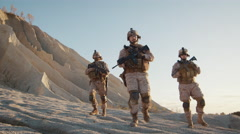 Squad of Three Fully Equipped and Armed Soldiers Walking in Desert  Stock Footage