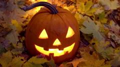 Halloween - a pumpkin lit upp by candles  surrounded by falling autumn leaves. Stock Footage