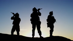 Squad of Three Fully Equipped and Armed Soldiers Standing in Desert Environment Stock Footage