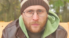 A bearded man in a sweater and leather jacket in the fall on a bench smoking a Stock Footage