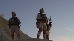 Squad of Three Fully Equipped and Armed Soldiers Standing on Hill in Desert  Stock Footage
