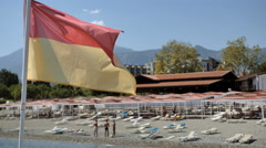 Pier with a lifeguard flag fluttering in a light breeze of Mediterranean sea Stock Footage