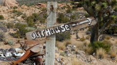 Zoom Out of Outhouse Sign blowing in the wind - Mojave Desert - Riley's Camp Stock Footage
